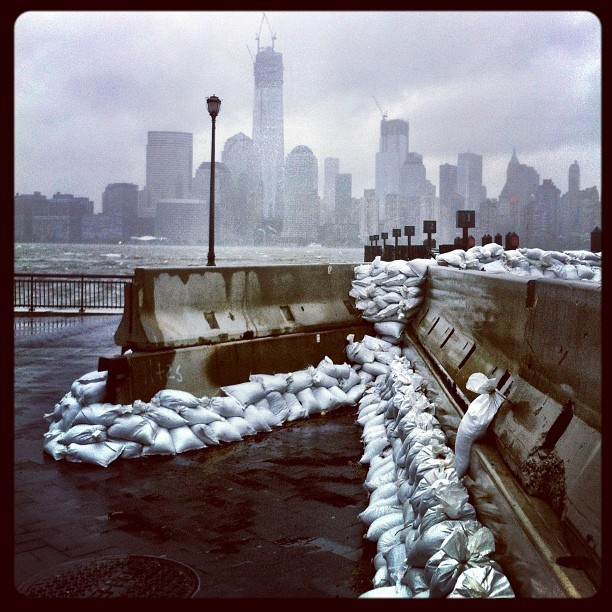 "Instagram User @time ""time #sandbags line the waterfront of downtown #jerseycity #newjersey with the unfinished Freedom Tower towering over lower #manhattan across the roiling #hudson #river"""