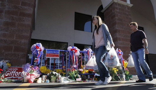 Shoppers at the Safeway in Tucson where the 2011 shooting took place. A small plaque memorializing the event was placed out front. Image Courtesy of AP Photo via LehighValleyLive.com