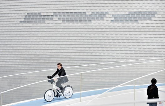 Bjarke Ingels cycling from the roof of the Danish Pavilion he design for the Shanghai Expo 2010. Image © Philippe Lopez