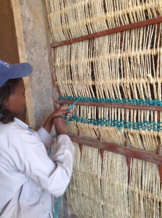 A hand-woven screen provides privacy for the cooking space. The use of vernacular materials and building practices in Rwanda is as much evidence of economic expediency as cultural concern.. Image © Yutaka Sho