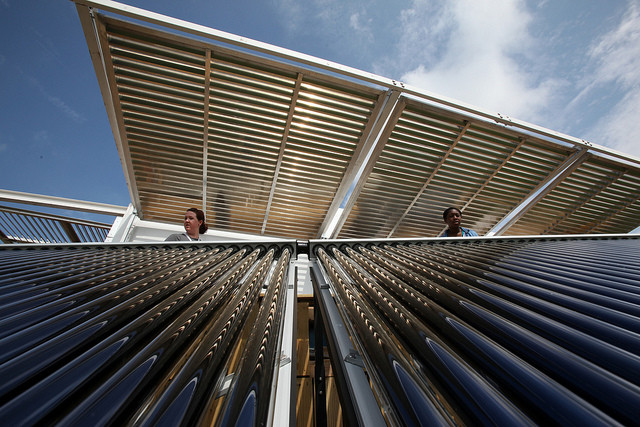 Brianna Bacon, right, and Lizzie DeLeonibus, left, of Maryland look out over Florida International University's solar thermal collector system at West Potomac Park in Washington, D.C., Wed., Sept. 28, 2011. Image © Stefano Paltera/U.S. Department of Energy Solar Decathlon