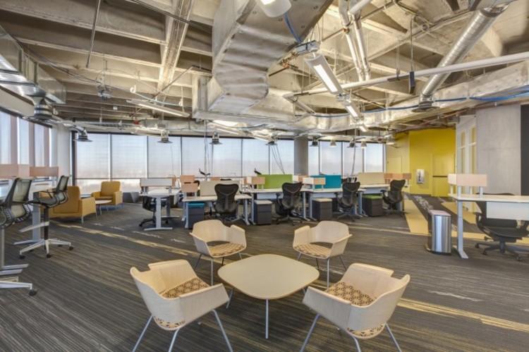 Zappos é uma das maiores companhias cujo funcionamento se baseia em princípios da 'holocracy' (sem uma hierarquia de equipe fixa). Sua sede em Las Vegas utiliza mobiliário coletivo para potencializar a colaboração da equipe (de acordo com a Business Insider, 'mesas são ligadas mas podem ser facilmente desconectadas ou movidas, as paredes são móveis também. Então se uma equipe precisa trabalhar de forma diferente, ou uma nova equipe é formada, o espaço pode ser alterado, e modificado novamente até que funcione'). Imagem Cortesia de Zappos, via OfficeSnapshots.com