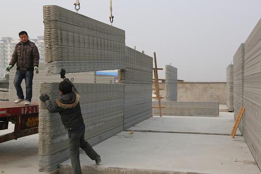 Oficina china imprime 10 Casas en 24 Horas, Trabajador ensamblando uno de los muros impresos. Image cortesía de Wall Street Journal
