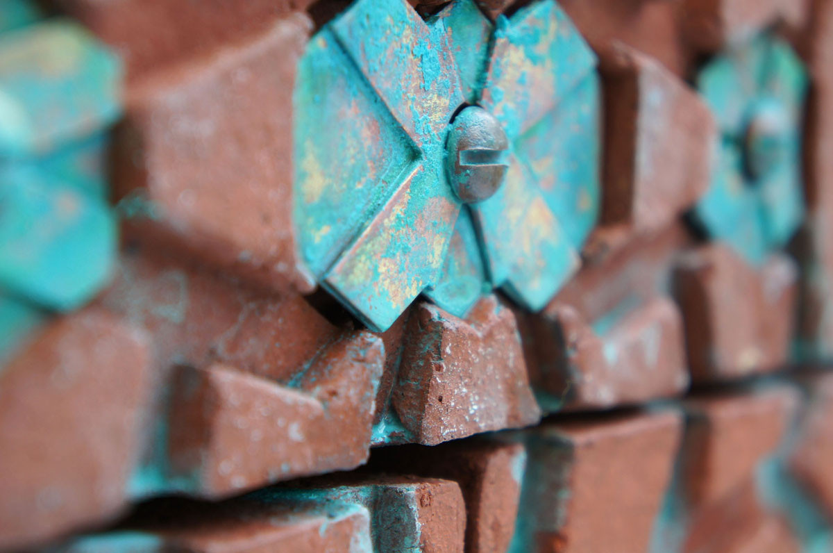 Cast brass lends a decorative verdigris to the red brick installations in the Smart by Nature project. Image Courtesy of Loekie Smeets