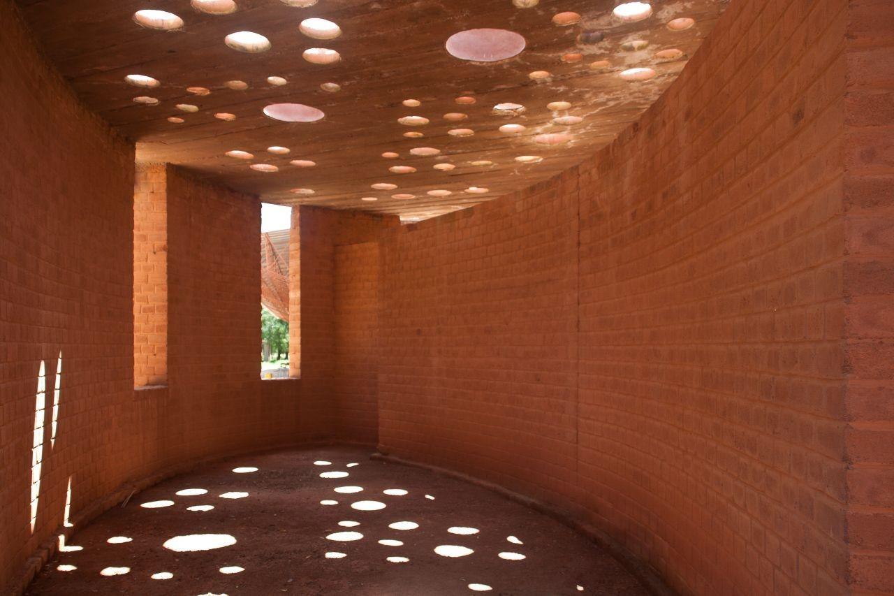 Ollas de arcilla integradas en la techumbre de la biblioteca escolar, genera una hermosa iluminación moteada low tech. Biblioteca escolar Gando  / Kere Architecture. Imágen cortesía de Kere Architecture