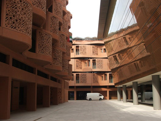 Masdar's Incubator Building banks away from its roof line to add pedestrian space while constructing the aperture between buildings above to limit the amount of sunlight hitting the street surface. Image © Tyler Caine