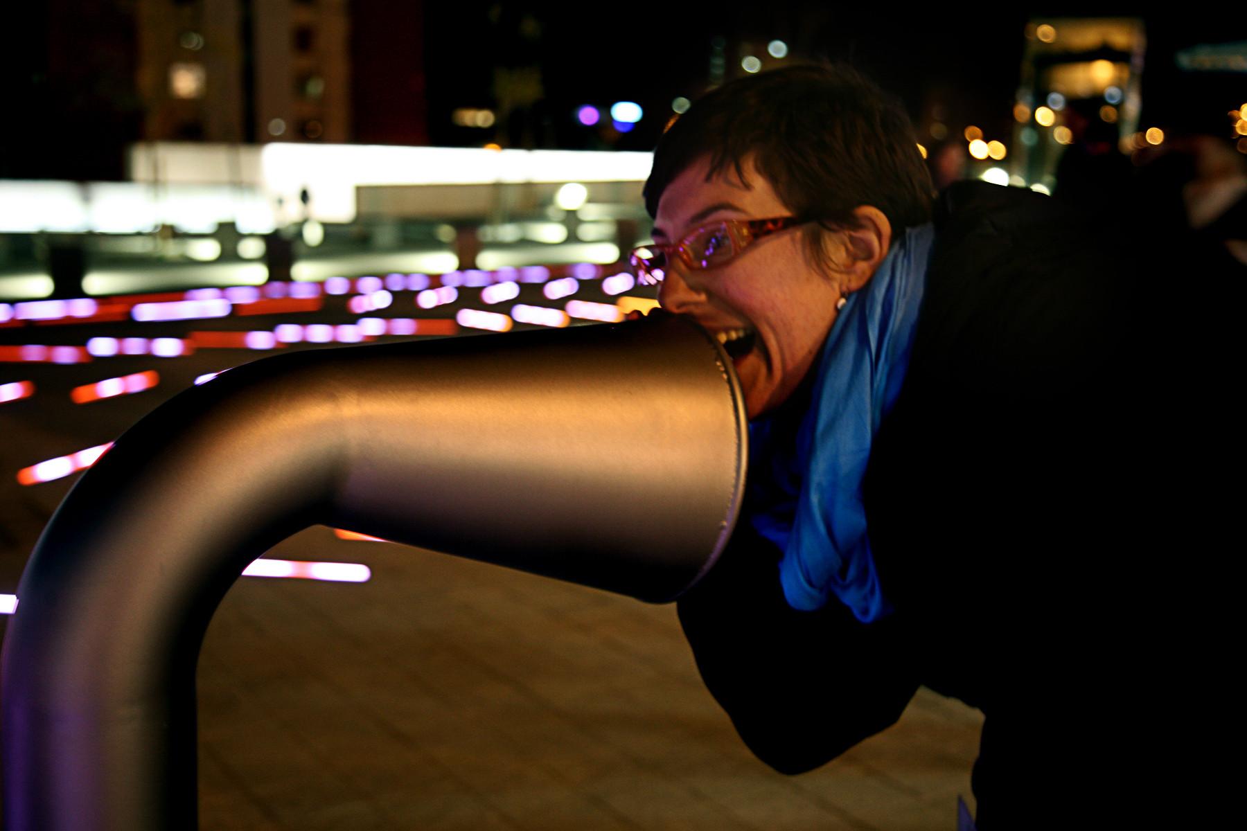 Un transeúnte gritando y sonriendo. La instalación interactúa con la intensidad de los gritos de los usuarios.. Image © Ramón Ferreira