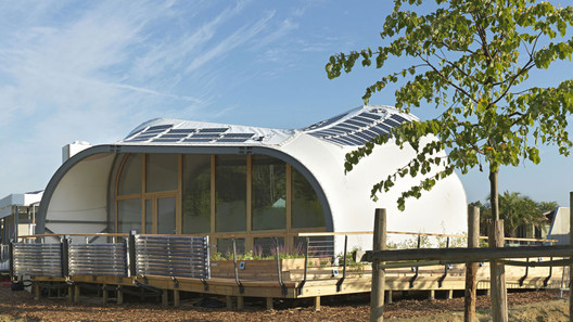 The planters filter rainwater, which is then reused to grow edible plants. Photovoltaic panels are arrayed along the curved roof. Image © Kristen Pelou