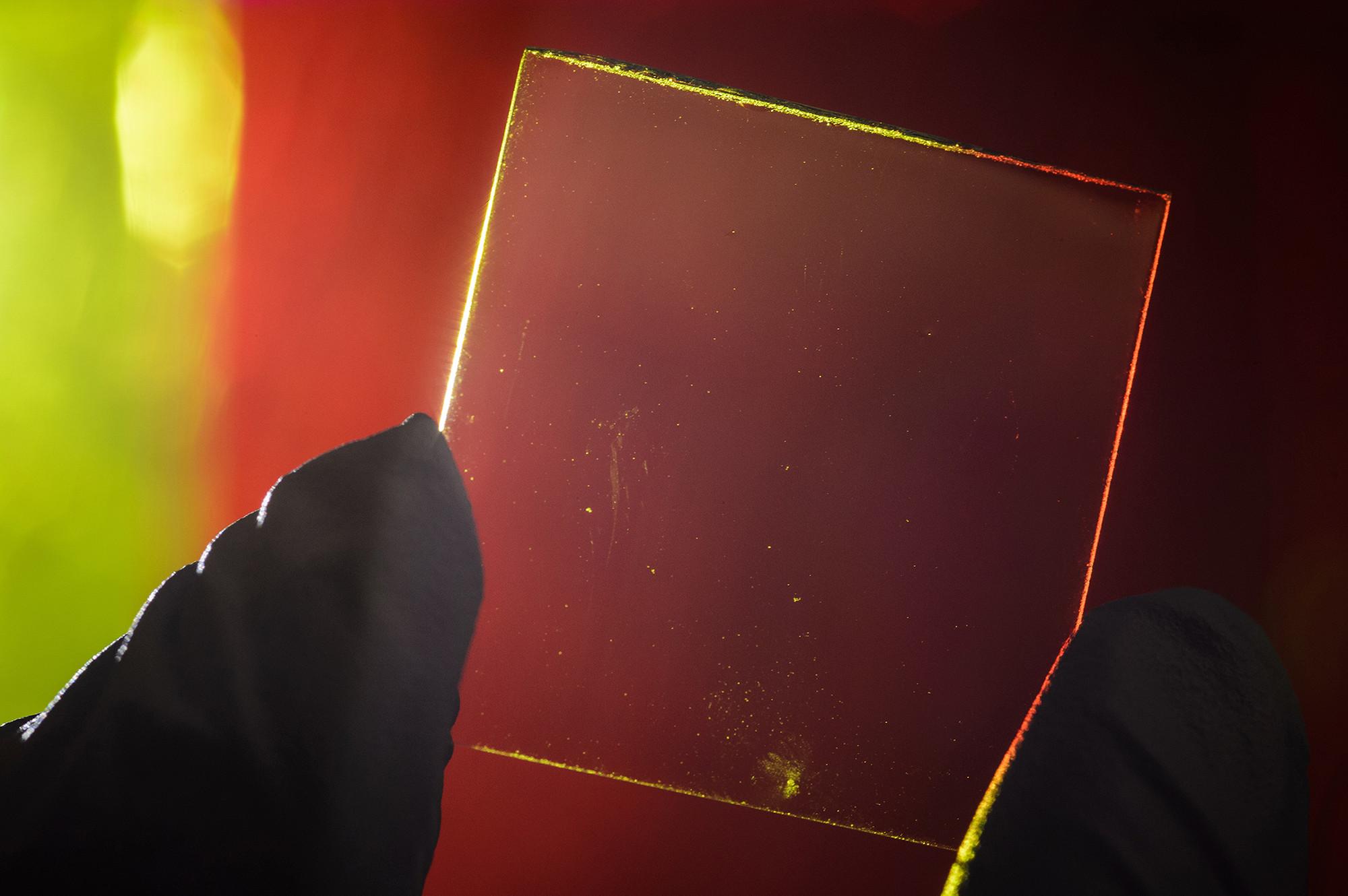 Un módulo transparente concentrador de luz solar es mostrado junto con un concentrado de luz solar tradicional de colores en el fondo. Imágen © G.L. Kohuth