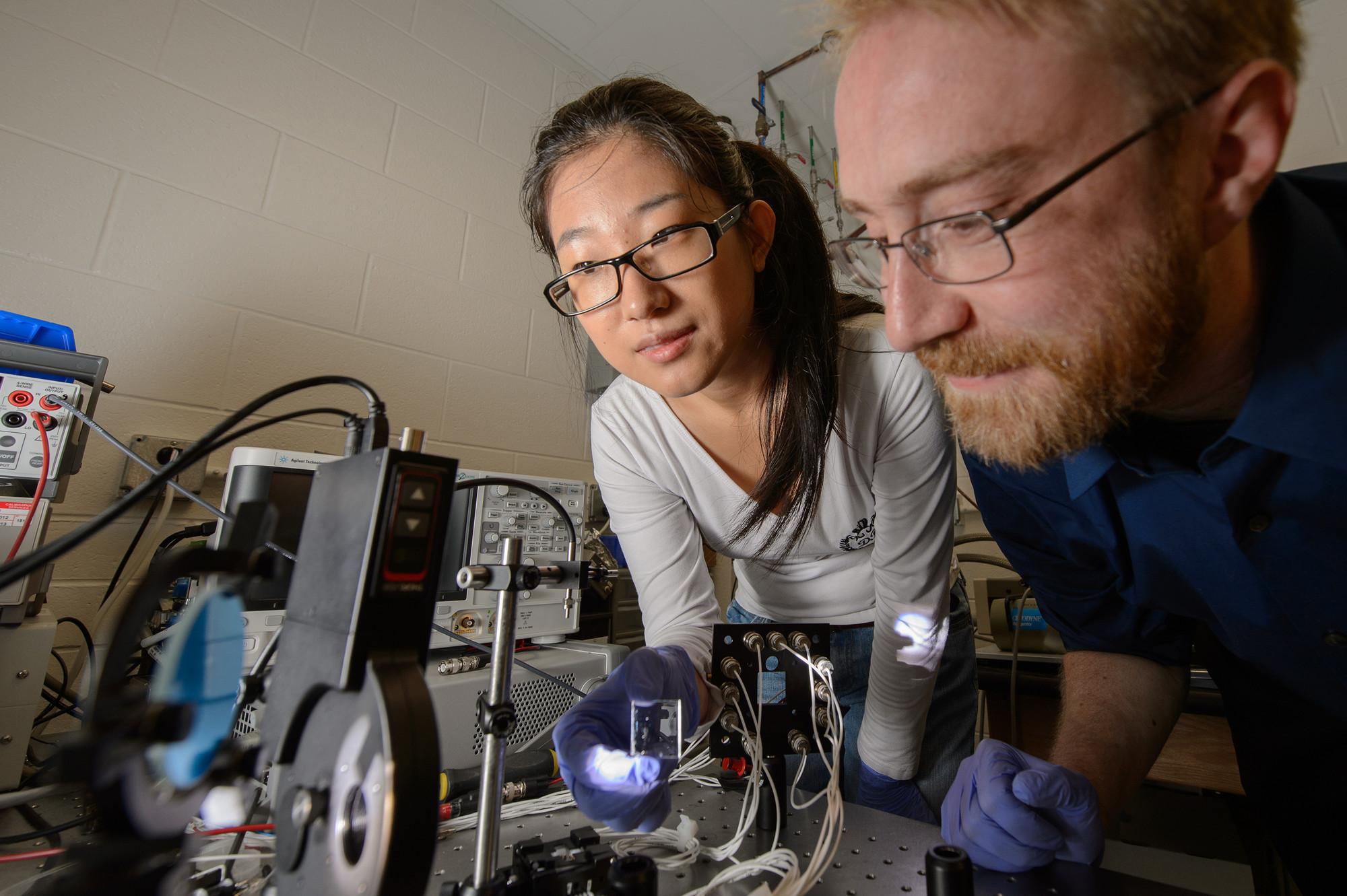 Yimu Zhao, estudiante de doctorado en MSU en ingeniería química y ciencia de los materiales, y Richard Lunt, profesor asistente de  ingeniería química y ciencia de los materiales , hacen un experimento en el laboratorio de Lunt. Imágen © G.L. Kohuth