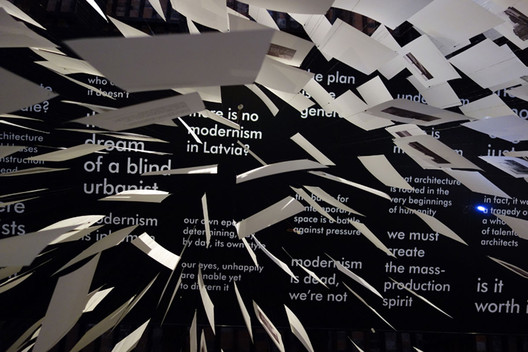 "A view from the floor of the Latvian pavilion. The sheets of paper carry images of Modernist buildings; the ceiling asks, ""There is no Modernism in Latvia"", commenting on the lack of historical scholarship. Image Courtesy of NRJA"