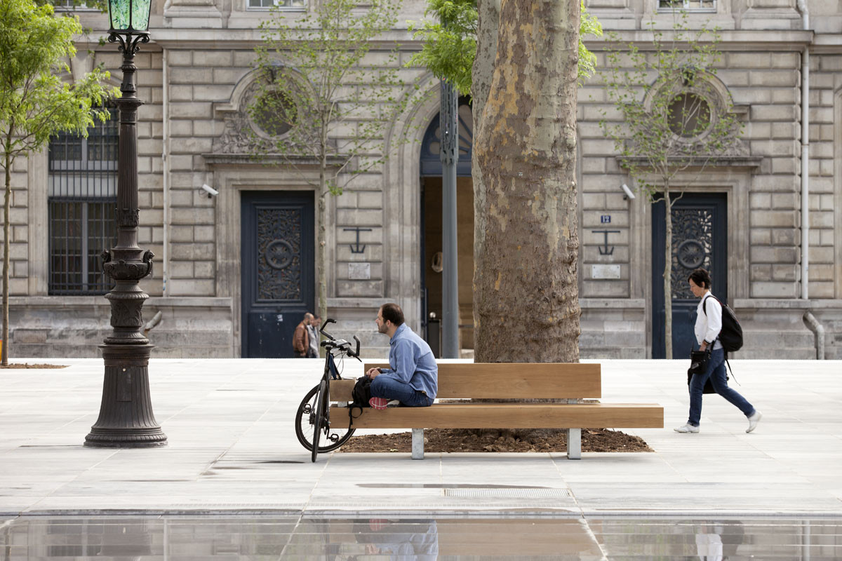 A cyclist watches Paris go by as he sits a while on one of the new benches installed in the plaza. Image © Clement Guillaume