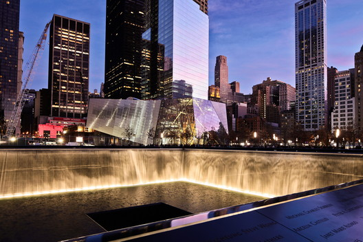 The National September 11 Memorial entry pavilion appears camouflaged against the backdrop of neighbouring glass curtain walls. Image © Joe Woolhead