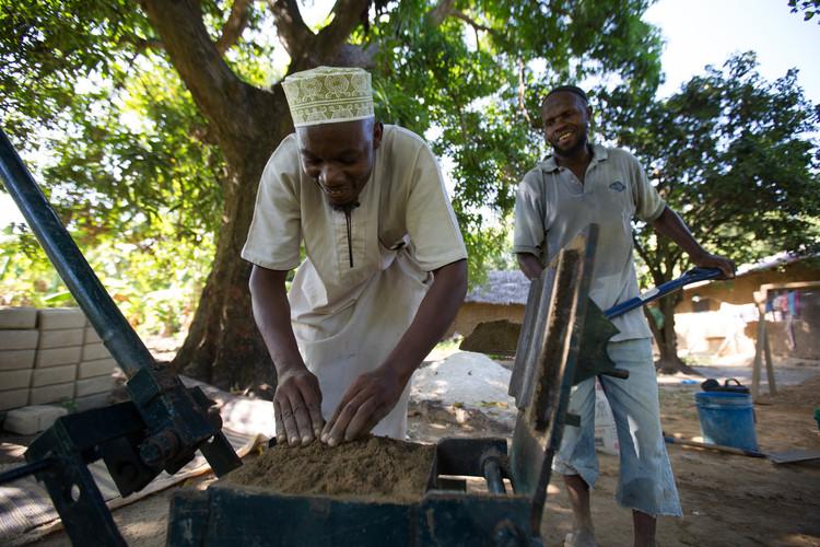 Fabricante local de bloques, Ali Cedric (izquierda) llena la prensa para los bloques. Imágen © Craig Norris