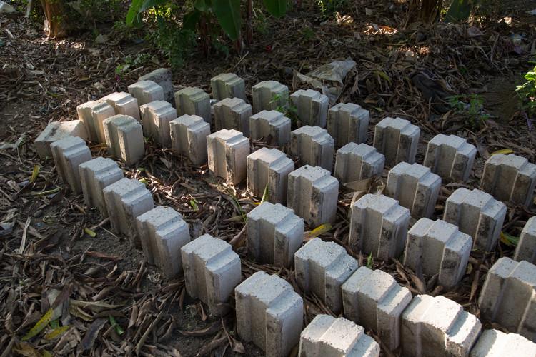 Pila de bloques de tierra. Estos son bloques experimentales que utilizan un agregado de coral, que es el subproducto de la extracción de bloques de coral en la isla. Imágen © Zach Melanson