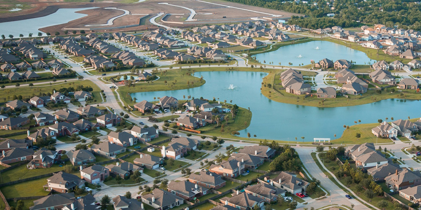 Suburbs like the Lakes of Savannah development in Houston are constructed around vast, meandering developments of 4,000-plus square foot houses on large lots, all stylistically prescribed. Image via lakesofsavannah.com