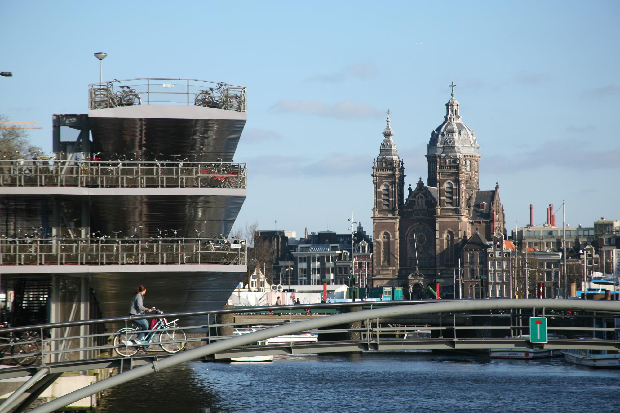 Estacionamiento de mútliples pisos frente a los muelles, puentes para ciclistas, la Estación Central de Ámsterdam y la Basílica de San Nicolás. Image © Steve Cadman [Flickr CC]
