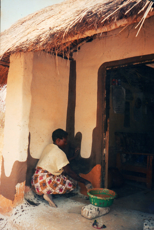Zambia: mujer enyesando muro. Imagen © Jon Sojkowski via Zambia Architecture