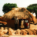 Zambia - thatch stored in bundles being applied to roof. Image © Jon Sojkowski via Zambia Architecture