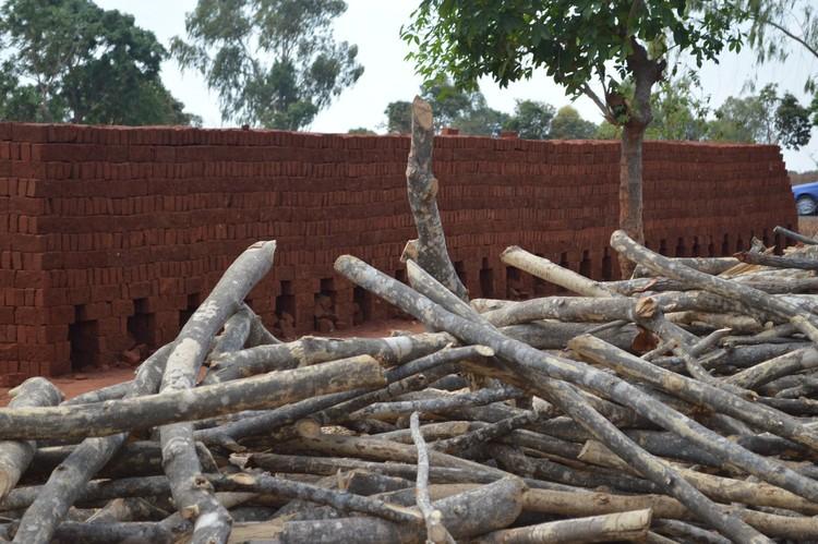 Malaui: un horno de ladrillos en el fondo, con la madera necesaria para quemarlos. Imagen © Jon Sojkowski via Malawi Architecture