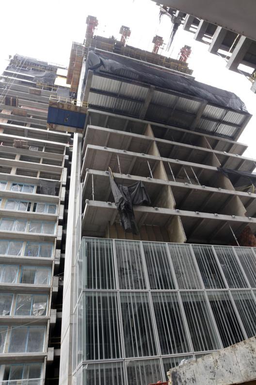 Instalación de termopaneles de la Torre Norte. Más arriba se distingue el avance de la construcción de uno de los puentes que conectarán ambas torres. Image © Nicolás Valencia