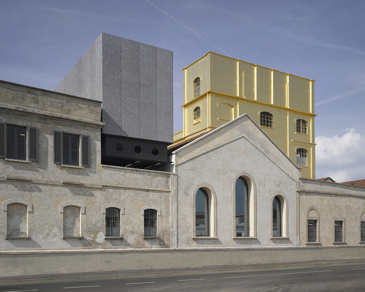 "The Fondazione Prada in southern Milan houses the fashion brand's namesake arts foundation, established by Miuccia Prada and Patrizio Bertelli more than two decades ago. Opened in May, the walled-in compound is a small city of culture, with a series of revitalized industrial buildings linked by de Chirico–like ""streets"" and piazzettas. Image © Bas Princen - Fondazione Prada"