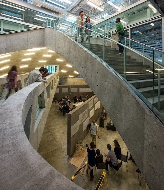 OMA's Milstein Hall at Cornell University shows off the dynamic atmosphere of an architecture school; as students on he ground floor have seminars and crits, other students mill above them. Image © Matthew Carbone