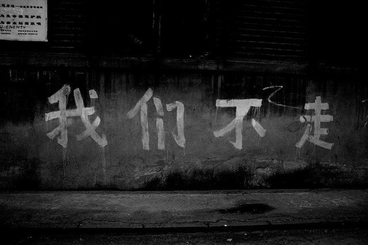 """We Will Not Leave""  Words painted on a wall in a neighborhood slated for demolition. Despite some protests, Beijing citizens were powerless to stop the demolition of their homes in the name of the Olympics. Photo via Flickr CC User theroadisthegoal"