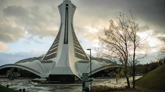 """Montreal's 1976 Olympic Stadium, nicknamed """"The Big O"""" and subsequently """"The Big Owe,"""" cost Montreal about 1 Billion Dollars due to construction and its ever-breaking retractable roof. Today, it sits empty. Photo by Gary Hustwit via Objectified."""