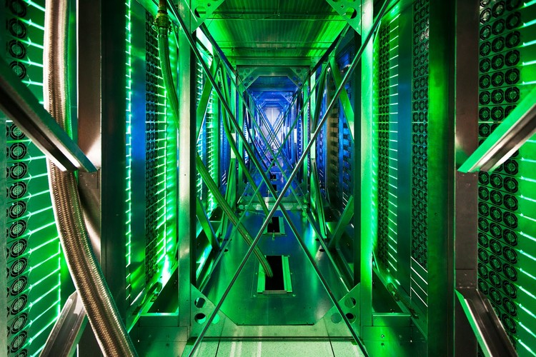 """A rare look behind the server aisle. Here hundreds of fans funnel hot air from the server racks into a cooling unit to be recirculated. The green lights are the server status LEDs reflecting from the front of Google's servers."" Photo © Google/ Connie Zhou"