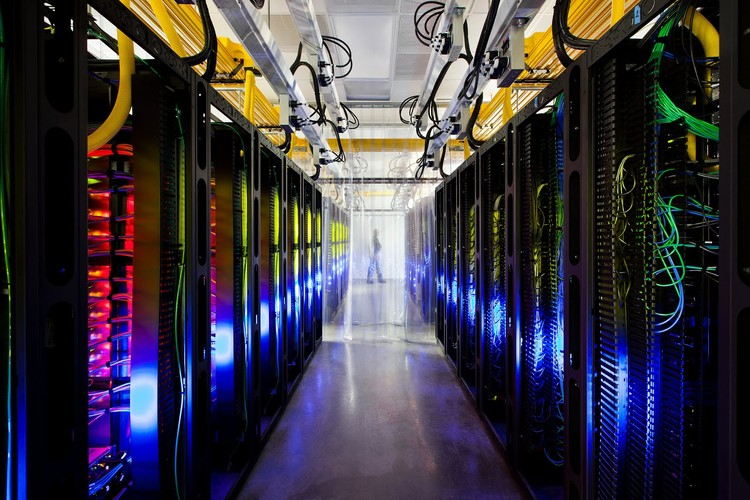 """Network Room at Google's Data Center in Council Bluffs: """"Inside Google's campus network room, routers and switches allow data centers to talk to each other. The fiber optic networks connecting their sites can run at speeds that are more than 200,000 times faster than a typical home Internet connection. The fiber cables run along the yellow cable trays near the ceiling."""" Photo ©Google/ Connie Zhou"""