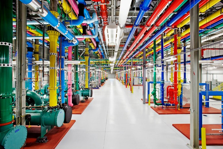 """Thousands of feet of pipe line the inside of Google's data centers. They paint them bright colors not only because it's fun, but also to designate which one is which. The bright pink pipe in this photo transfers water from the row of chillers (the green units on the left) to a outside cooling tower"" Photo © Google/Connie Zhou"