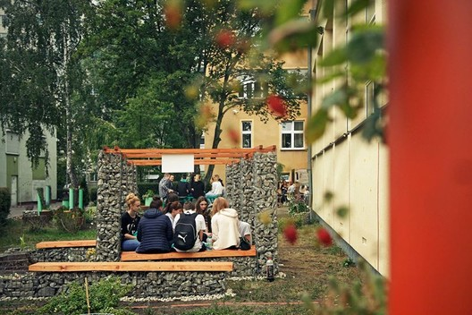 The open air classroom in front of the school building. Open air classroom contains banches and arbor made of gabions filled with stones.