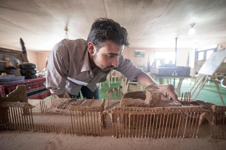 Artistas sirios construyen réplicas de monumentos destruidos en su país, Mahmoud Hariri construyendo un modelo de Palmira utilizando arcilla y brochetas de kebab. Imagen cortesía de UNHCR Tracks