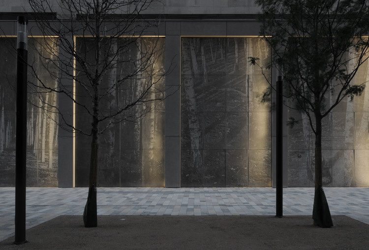The textured surface of the frieze changes according to ambient light, creating a perplexing effect in the image from day to night. Image Courtesy of Lynch Architects