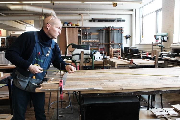 El estudiante de arquitectura de Waterloo, Bradley Paddock mide para cortar la puerta de la cámara de gas de la maqueta. Imagen © Fred Hunsberger