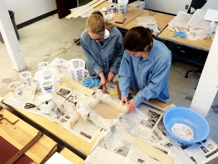 Los estudiantes de Waterloo, Anna Beznogova y Anna Longrigg preparan un molde de fundición. Imagen © Piper Bernbaum