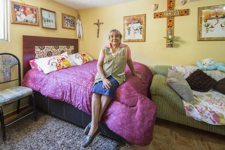 Doña Karitina posa para un retrato en su cama. Administra un puesto de verduras en el patio de su casa y cuenta con el apoyo de su esposo para despachar a los clientes. Febrero, 2016.. Image © Livia Radwanski
