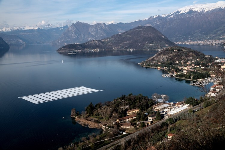 Febrero 2016: Vista aérea del lugar de la construcción del proyecto en la península Montecolino y la zona de aparcamiento para los 30 módulos de 100 por 16 metros en el Lago Iseo . Image © Wolfgang Volz