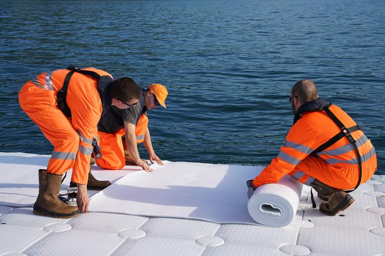 Mayo 2016: Los trabajadores instalan el fieltro que cubrirá los cubos flotantes antes de instalar la tela amarilla. Image © Wolfgang Volz