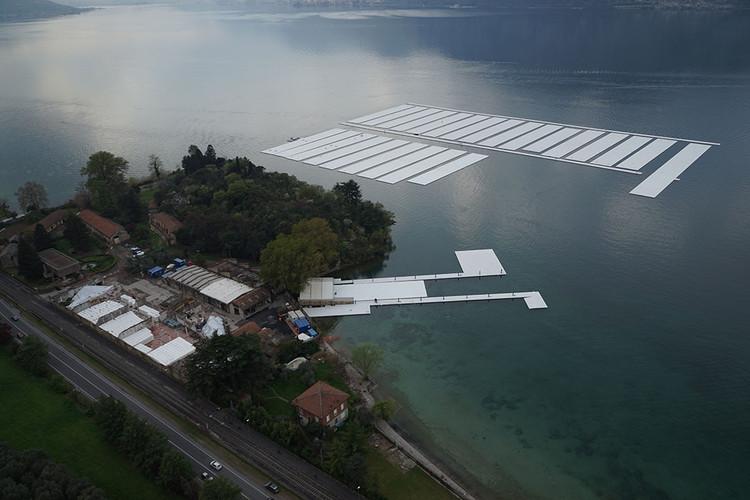 Abril 2016: Vista aérea del centro de construcción del proyecto en la península Montecolino y la zona de aparcamiento para las secciones de 30 módulos de 100 por 16 metros en el Lago Iseo . Image © Wolfgang Volz