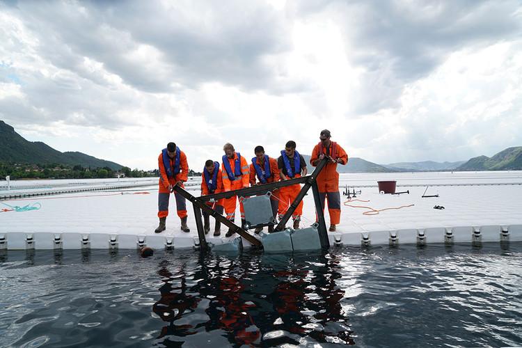 Abril 2016: Los trabajadores empujan uno de los marcos debajo de un elemento flotante antes de conectarlo con tornillos. Image © Wolfgang Volz