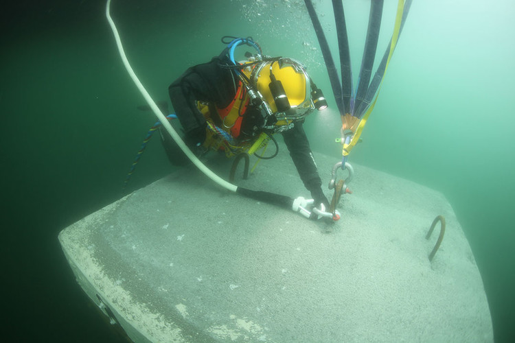 Marzo 2016: Un buzo conecta una cuerda hecha de polietileno de alto peso molecular (UHMWPE), cubierto con una capa protectora de poliéster con una carga de rotura de 20 toneladas métricas, a una de las anclas en el lecho del lago para mantener los muelles en su lugar. Image © Wolfgang Volz