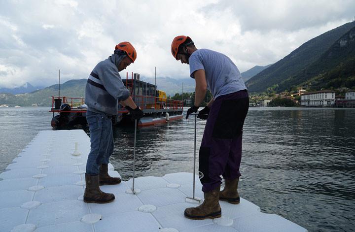 Trabajadores de la construcción ensamblan los primeros segmentos flotantes conectando los cubos de polietileno entre sí.. Image © Wolfgang Volz