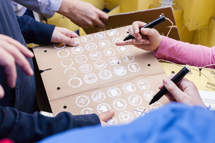 Los visitantes interactúan con la instalación, depositando sus sueños e ideas en las mismas piezas de cartón que arderán el último día.. Image © Milena Villalba