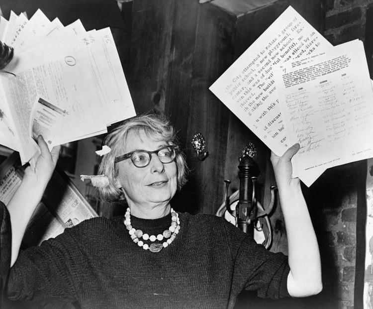 Cities Need Change: The Durability of Jane Jacob's Legacy, Mrs. Jane Jacobs, chairman of the Comm. to save the West Village holds up documentary evidence at press conference at Lions Head Restaurant at Hudson & Charles Sts. (1961). Public Domain