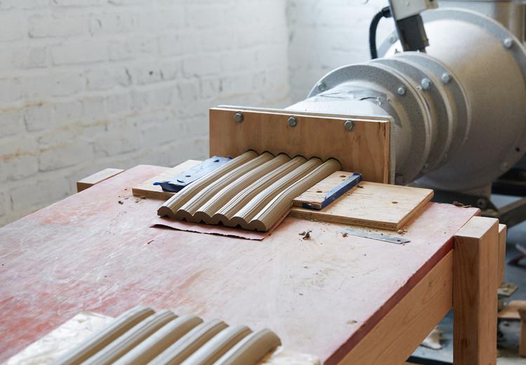 El taller de la fábrica contiene una extrusora de arcilla y un horno eléctrico. Imagen Cortesía de Sam Nixon