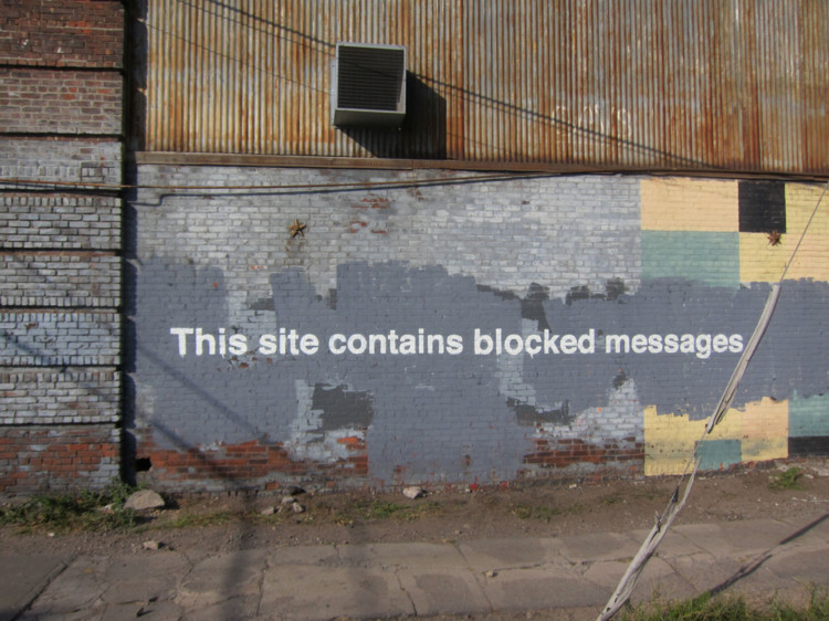 """Banksy's """"This site contains blocked messages,"""" an artwork completed during his much-publicized stay in New York. Image © <a href='https://www.flickr.com/photos/scottlynchnyc/10526310184/'>Flickr user scottlynchnyc</a> licensed under <a href='https://creativecommons.org/licenses/by-sa/2.0/'>CC BY-SA 2.0</a>"""