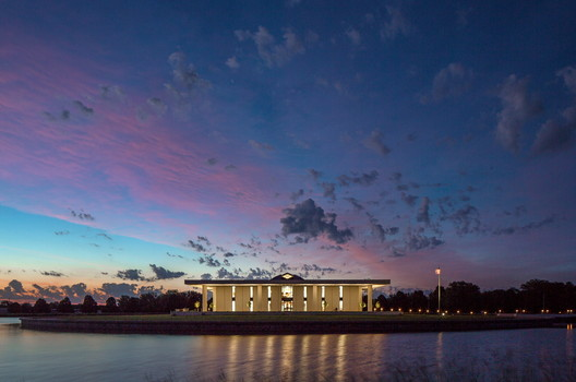 Stuhr Museum of the Prairie Pioneer: View at dusk of the west side of the Stuhr Museum of the Prairie Pioneer, featuring the square geometry of the museum by Edward Durell Stone, centered on the round island and pond designed by Edward Durell Stone Jr.. Image © Tom Kessler Photography, 2016