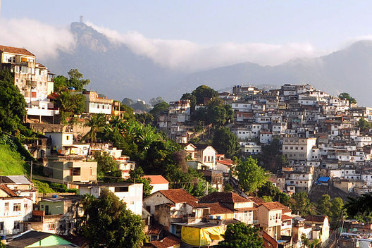 In the background you can see the Santa Teresa Favela in Rio de Janeiro, in contrast to the wealthy neighborhood in the foreground. Image via Wikimedia Commons User chensiyuan